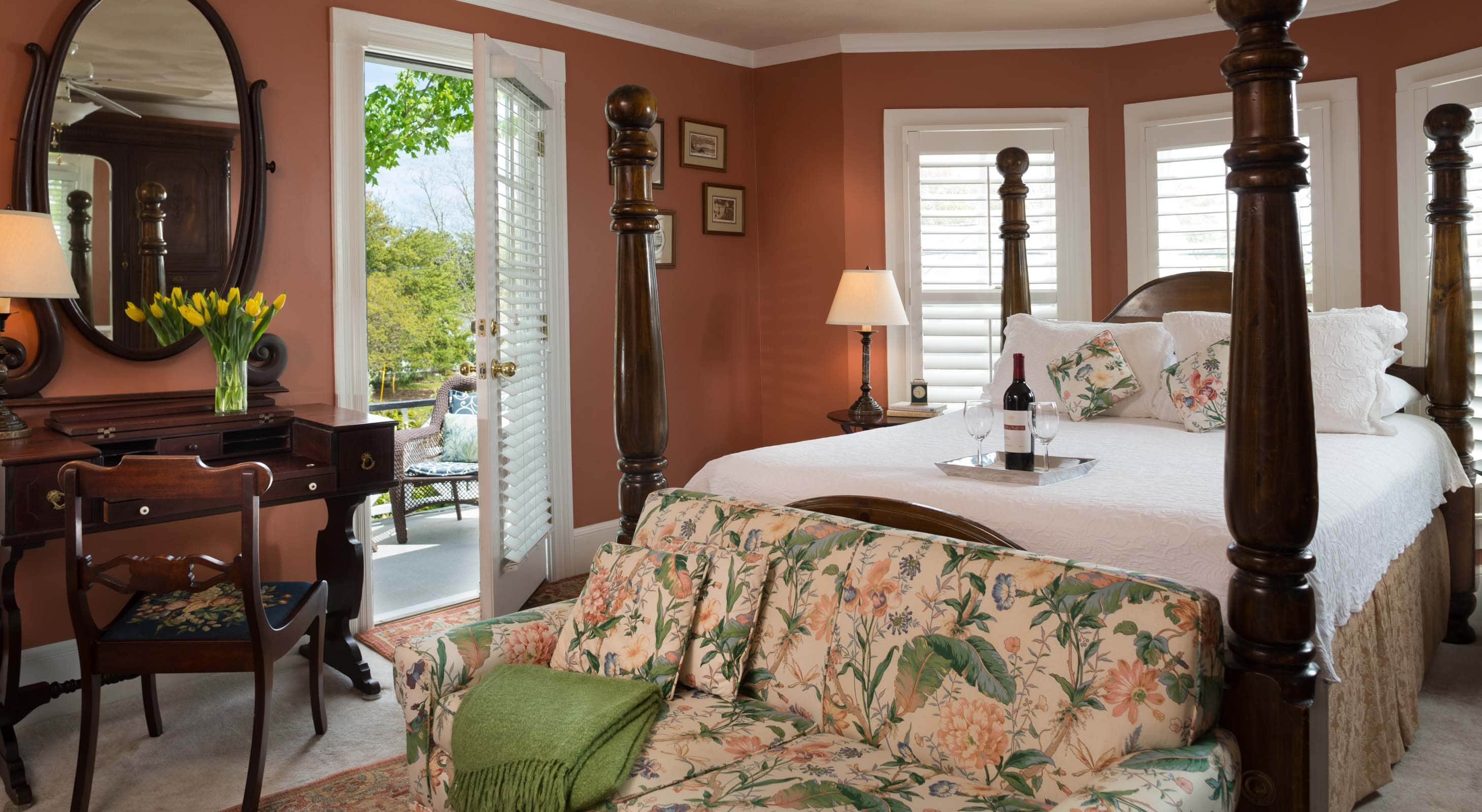 Raleigh room at White Doe Inn with a four poster queen bed, writing desk, and a door to private balcony