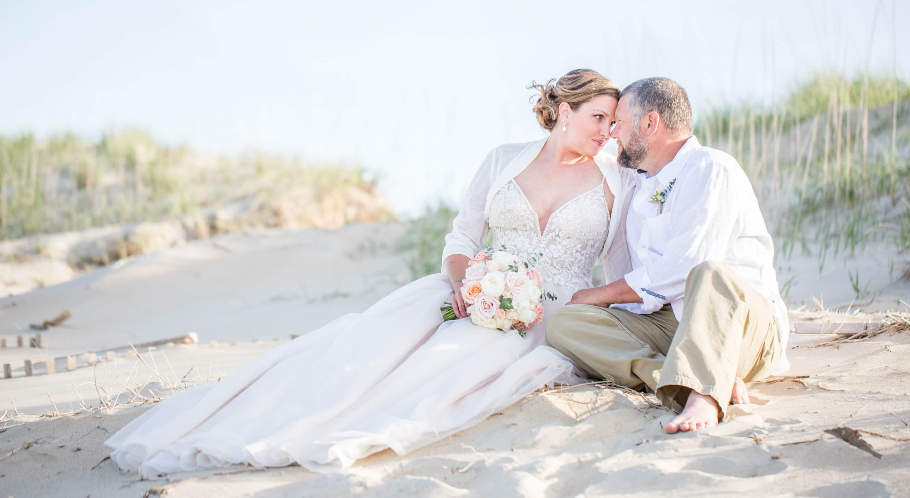 Bride and Groom sitting on a beach in the Outerbanks