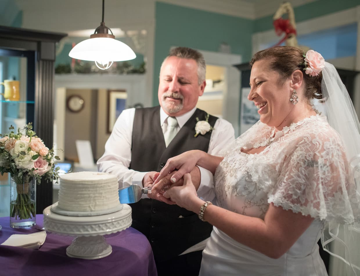 Bride and Groom Cutting the Cake at Our Outer Banks Wedding Venue