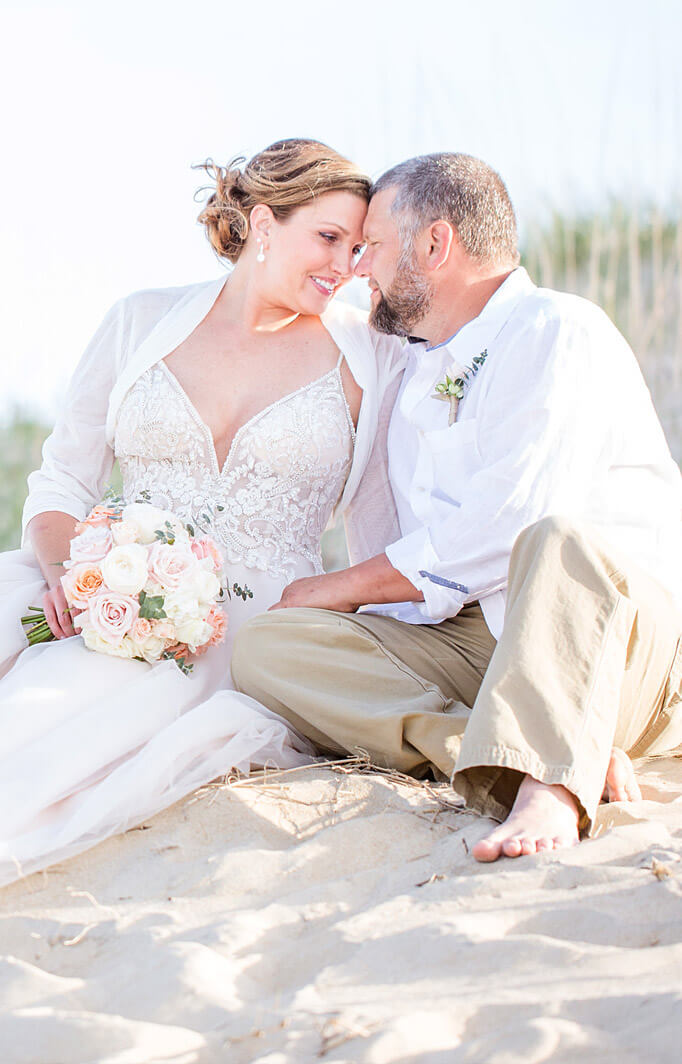 wedding couple sitting in the sand