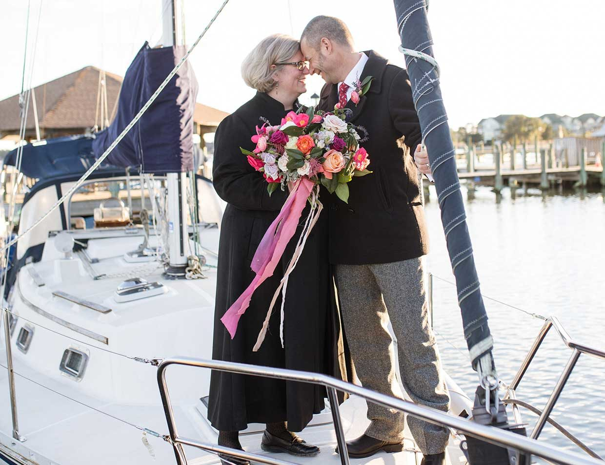 Couple with wedding bouquet eloping on a boat