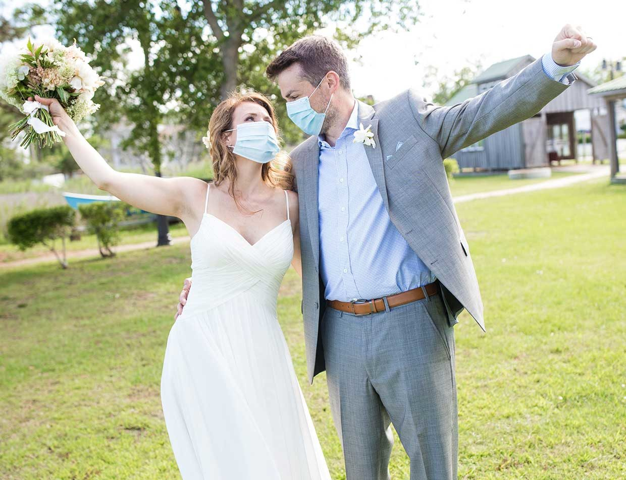 Married couple in masks with wedding bouquet