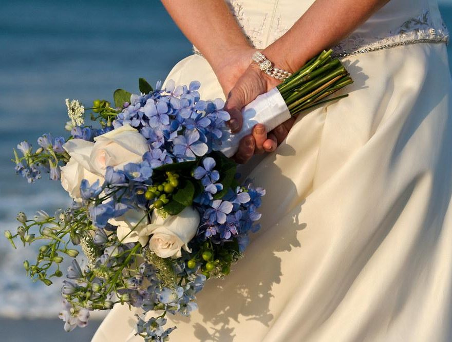 Bride holding a white, green and blue bouquet