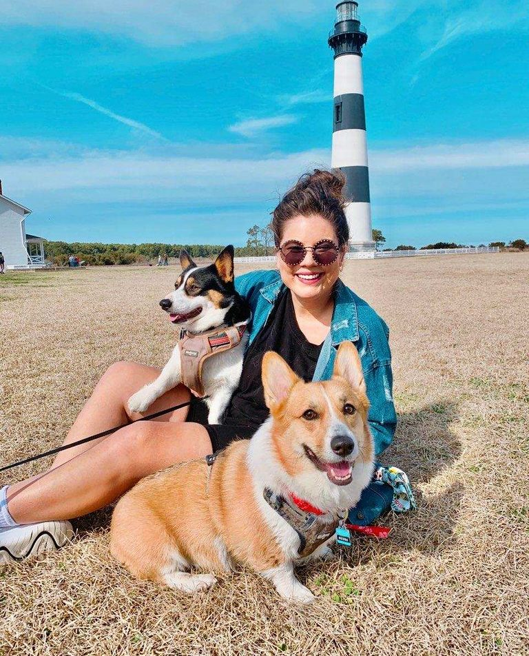 young smiling girl with two corgi dogs sitting on grass in front of lighthouse