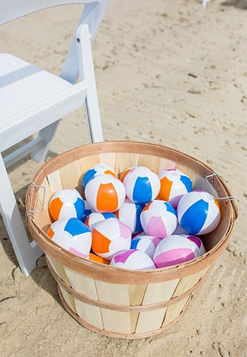 Mini Multi-colored beach balls in a basket basking in the sun on the beach next to a chair.