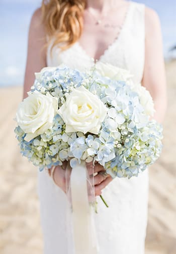 Wedding Bouquet of white rosees and small blue flowers held by bride on beach.