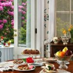 Table of colorful breakfast dishes on white plates and pink flowers outside open French doors