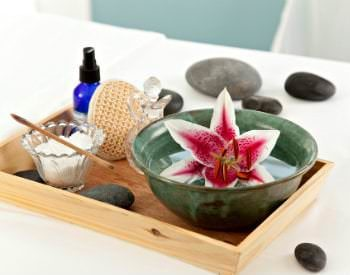 A beautiful lily floats in a bowl next to other spa items in a bamboo tray