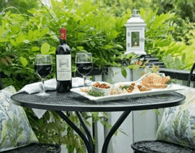 A plate of food, a bottle of wine and two glasses sit on this black bistro table on the patio