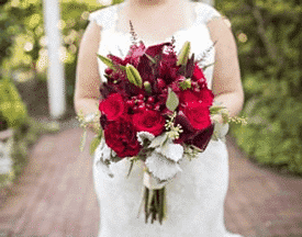 A bride stands holding a beautiful red, burgandy and green bouquet