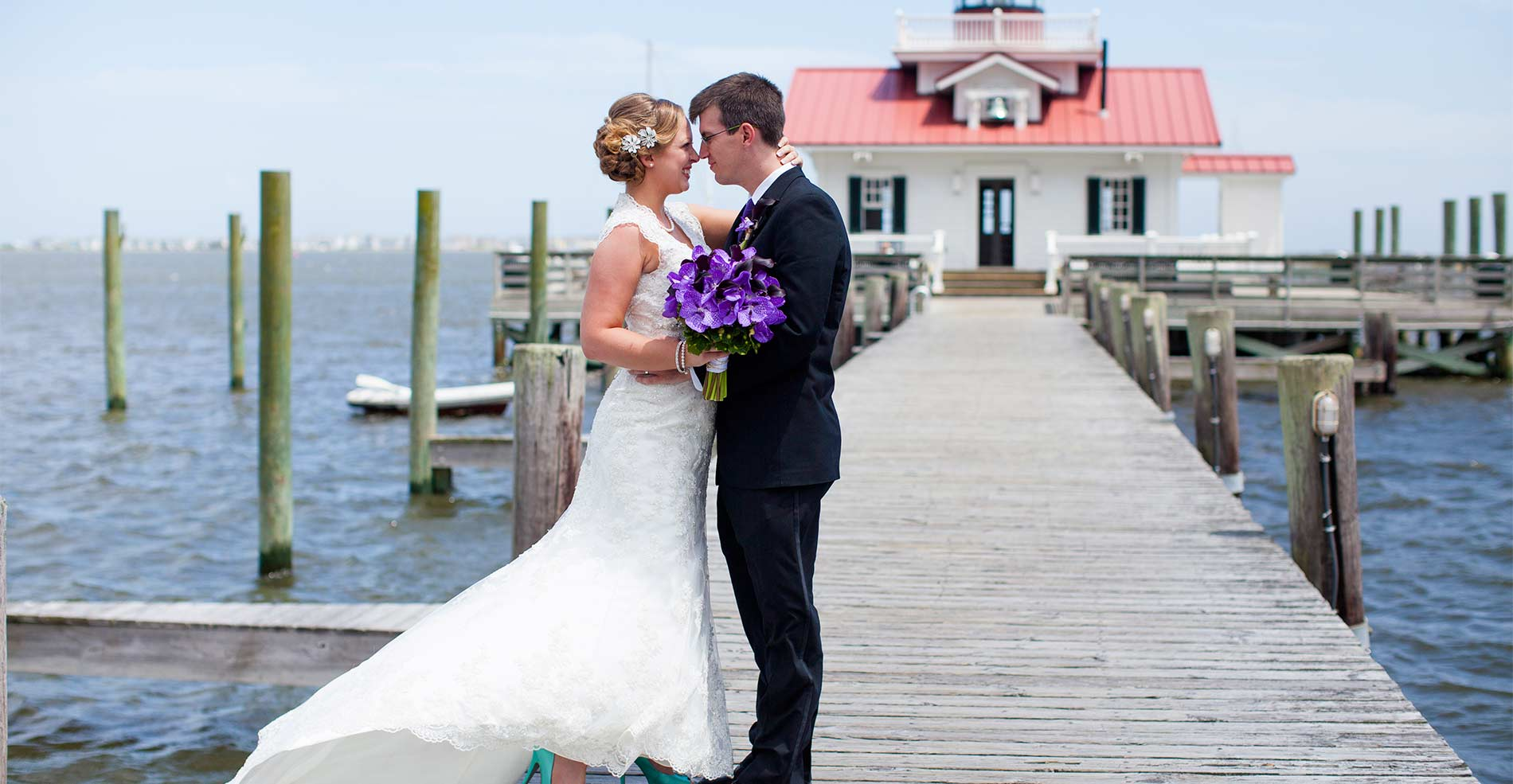 Wedding couple standing on pier with purple floral bouquet in hand between them. A little red building marks the background, set aganst the water.