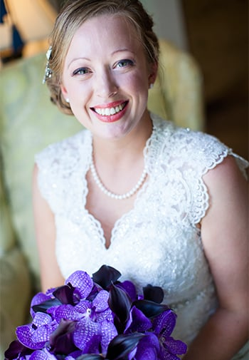 Woman in wedding dress holding purple floral bouquet.