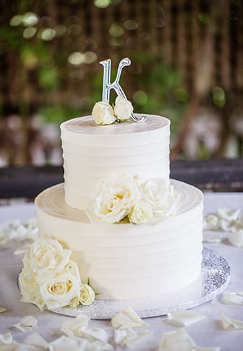 Wedding Cake with K on top, and beige flowers decorating the white dual tier cake, and plate.