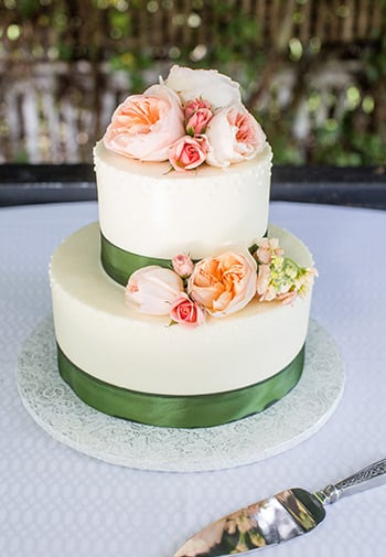 Two Tiered Wedding Cake with green ribbons, and multicolored flowers.