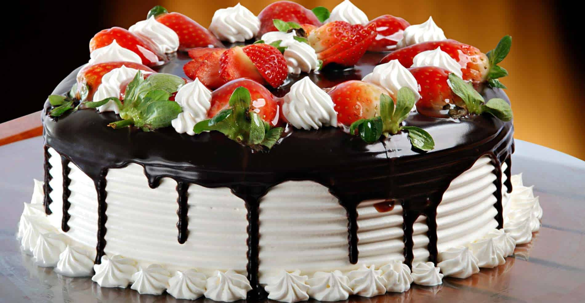 A delicious white cake with chocolate dripping down the sides, topped with red strawberries and cream