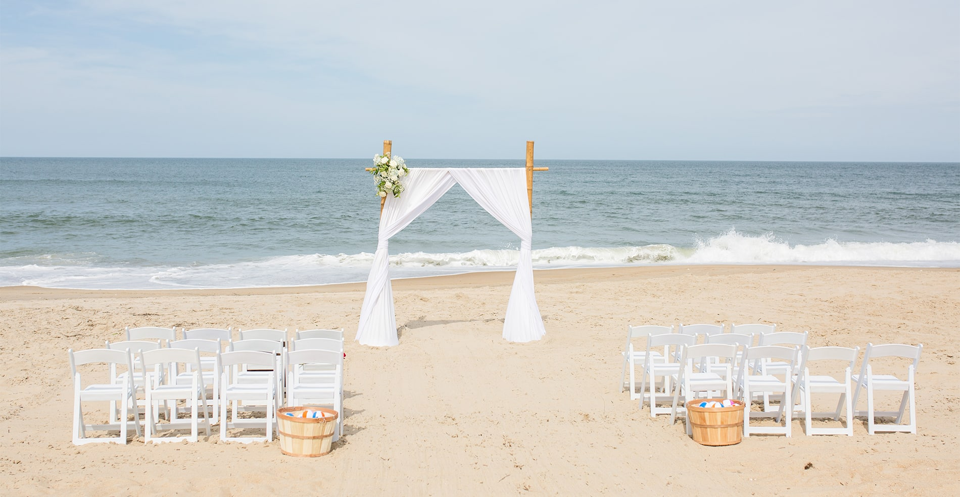 "Wedding Arch on beach with chairs set up on either side of the ""aisle""."