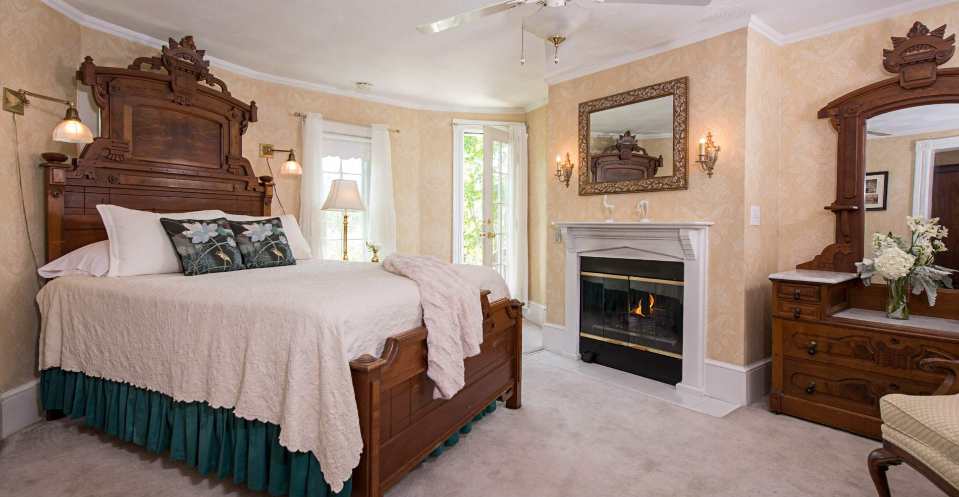 In a warm cozy room a Large white bed with green accents sits across from a beautiful wardrobe and fireplace