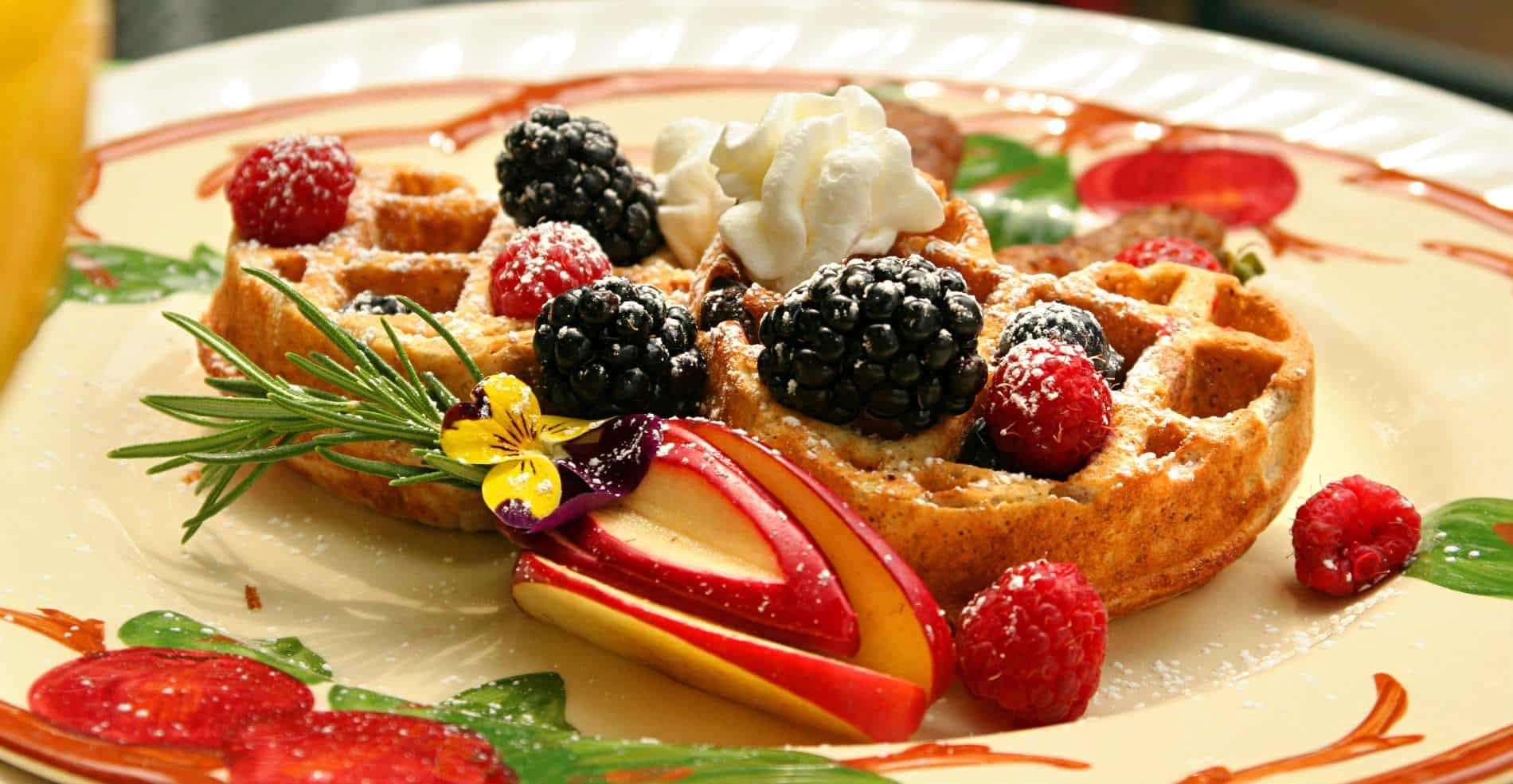 A close up of golden brown waffles covered in fresh red and blackberries