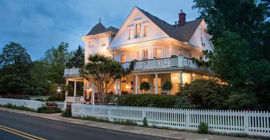 Large, white Inn at dusk with glowing lights lighting up the exterior and a white picket fence surrounding the Inn