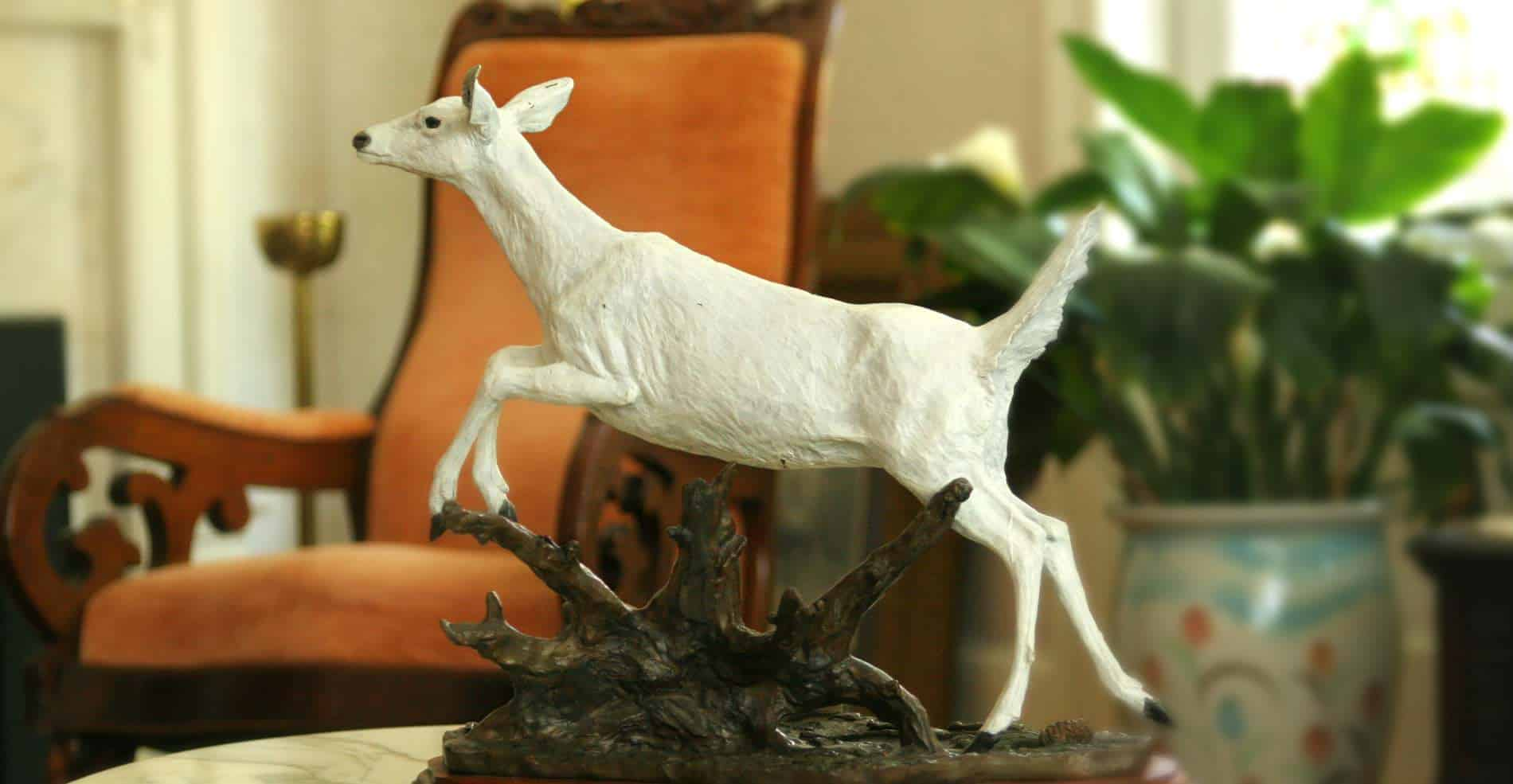 A close up of a small white doe statue, an orange chair and bright green plant in background