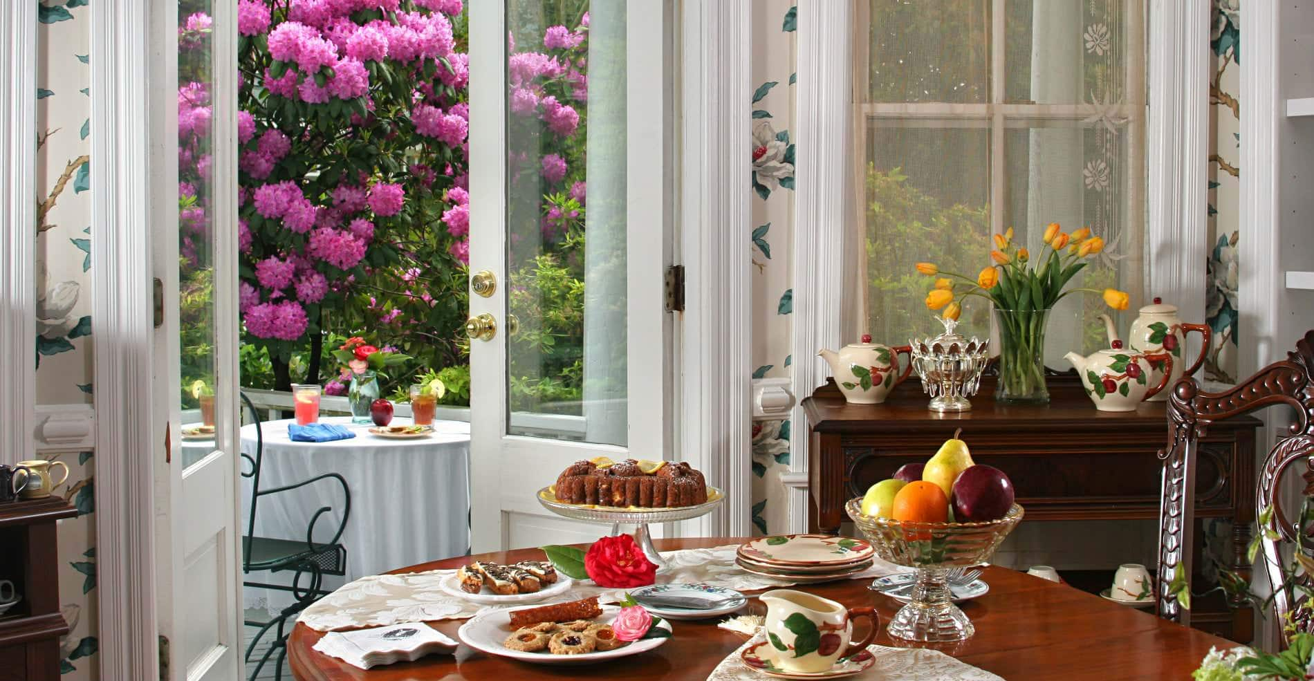 Table of colorful breakfast dishes on white plates with pink flowers outside open French doors