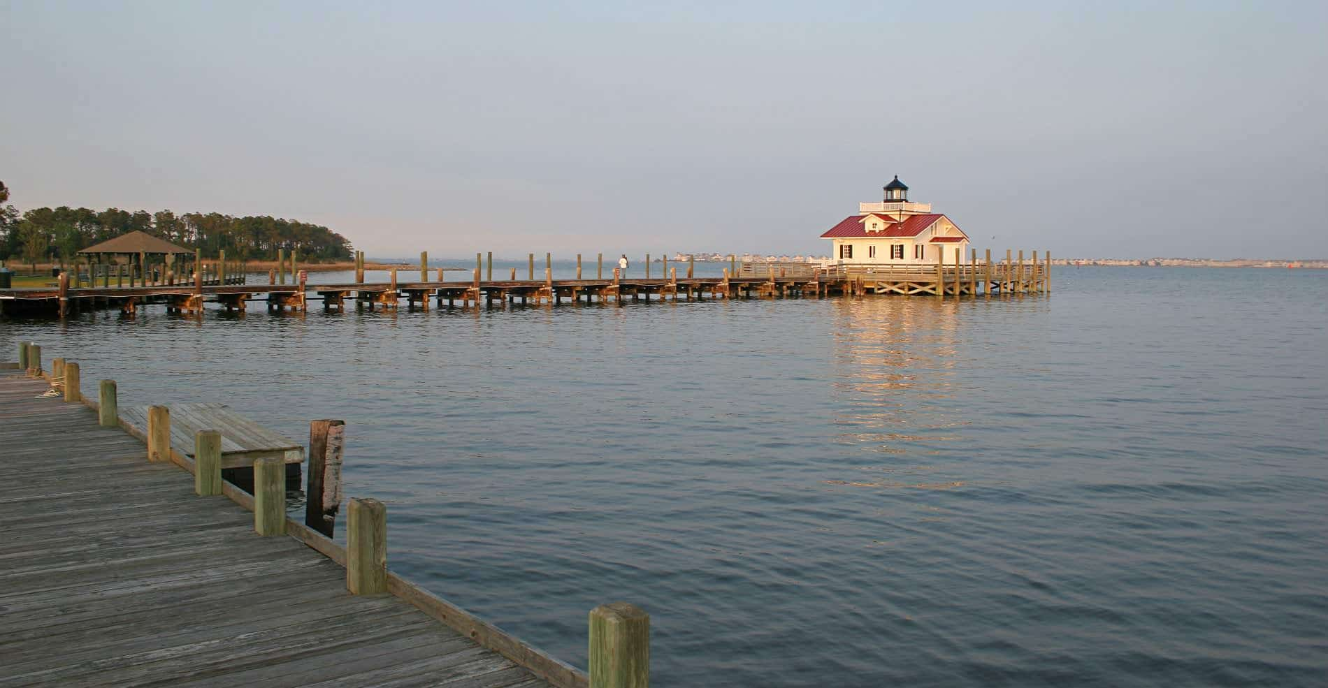 A beautiful view of a small white building with a red roof at the end of the pier, overlooking the water