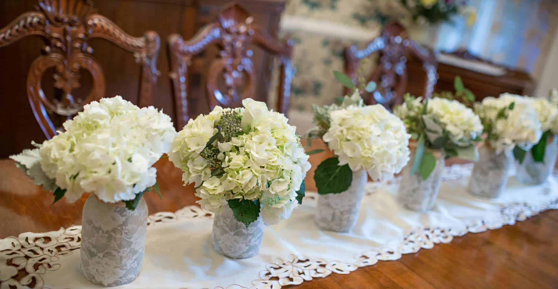 On a large table, small arrangemtents of white flowers line the center of the table on a white runner