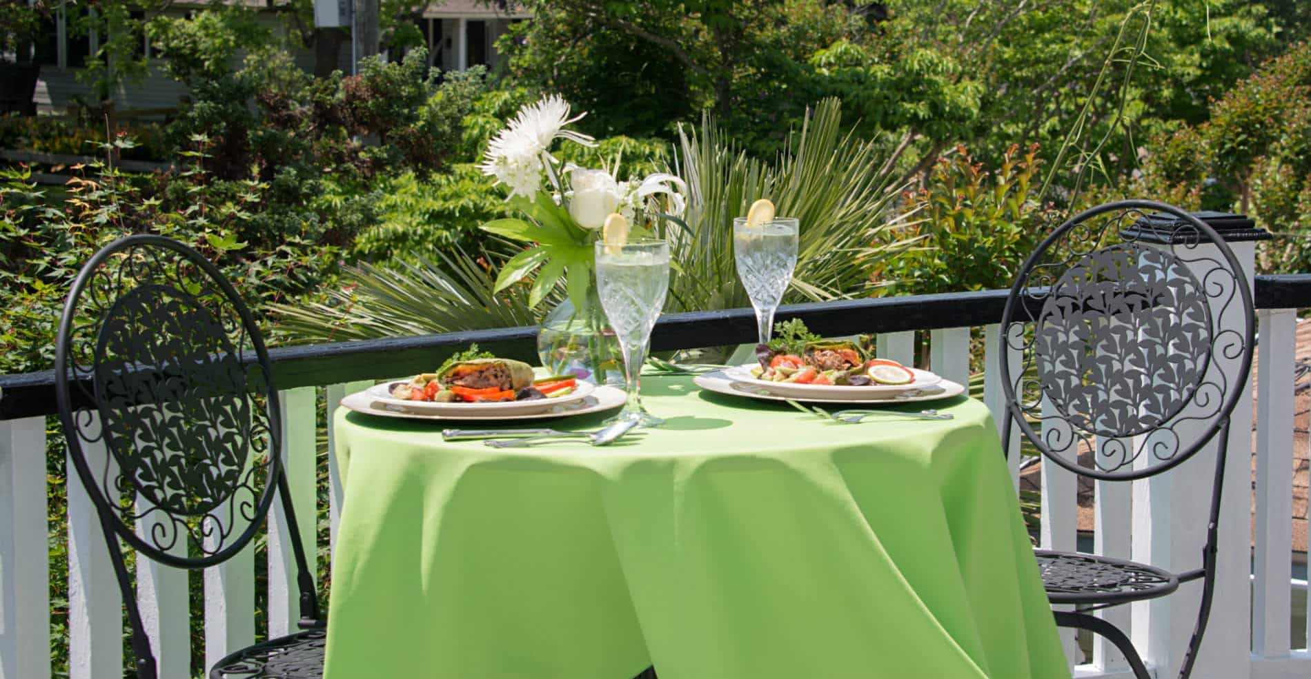 On a patio is a small bistro table with a green table cloth is a meal set for two