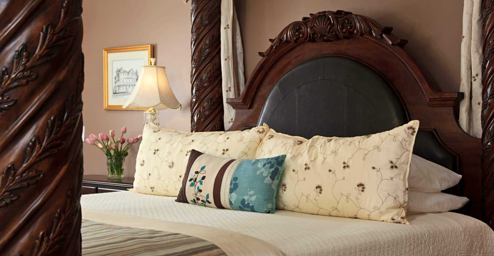 A close up of a big  dark brown beautiful four post bed with cream colored pillows