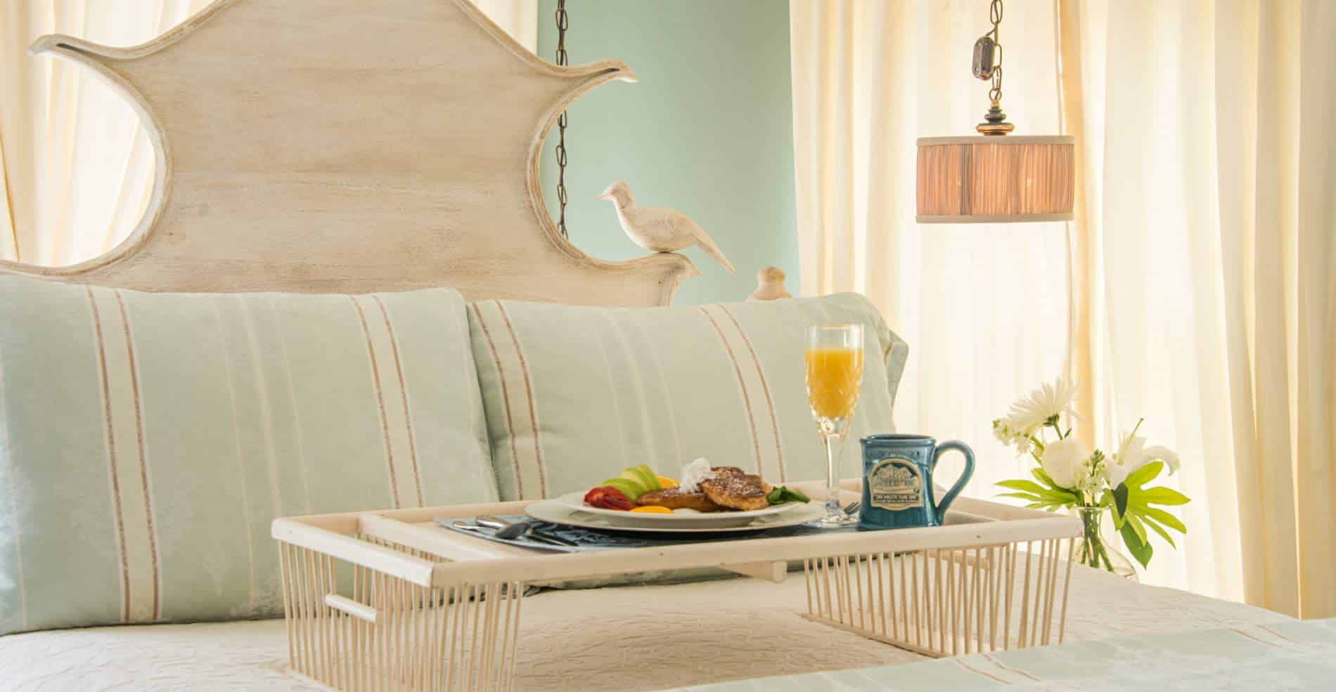 In a light and comfy room, a breakfast tray sits on a bed, with a plate of food, a glass of orange juice and a blue coffee cup