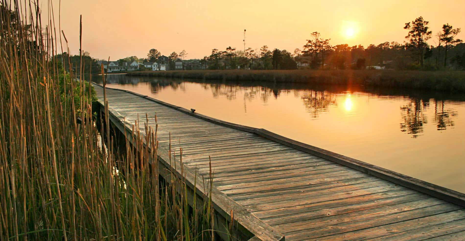 A beauitful and secluded view of the sunset from a wooden pier overlooking the water