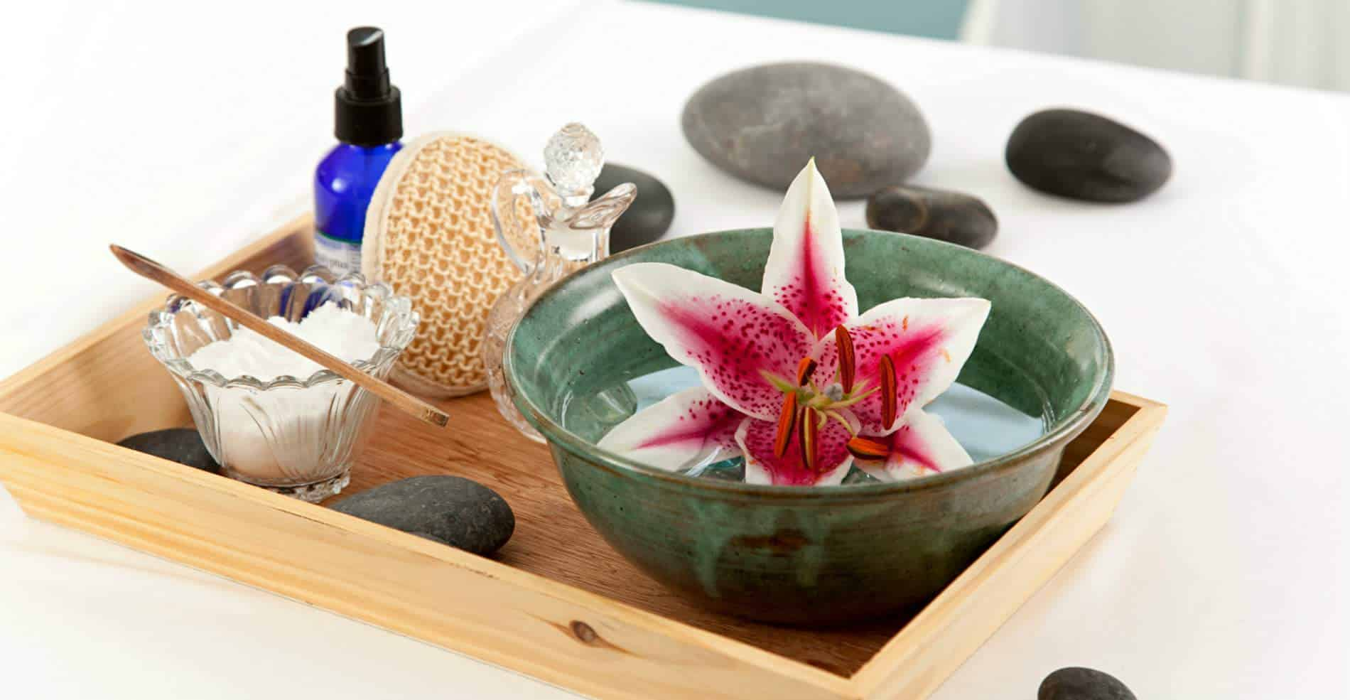 On a small wooden tray is an assortment of spa amenities, and floating in a bowl of water is a big red and white lily