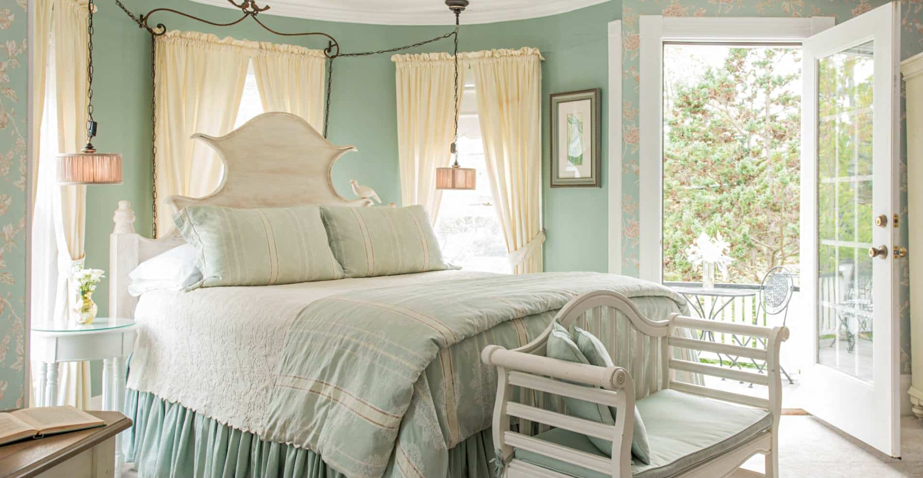 In a teal and white colored room is a well made bed, with an open door leading to the patio
