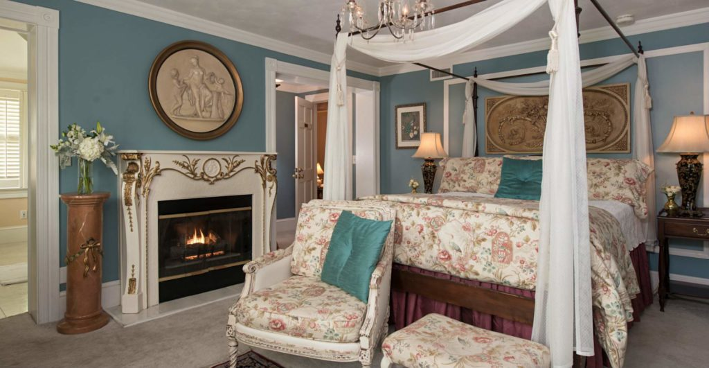 Colonial blue and white room with canopy bed, floral bedding, and a cozy fireplace