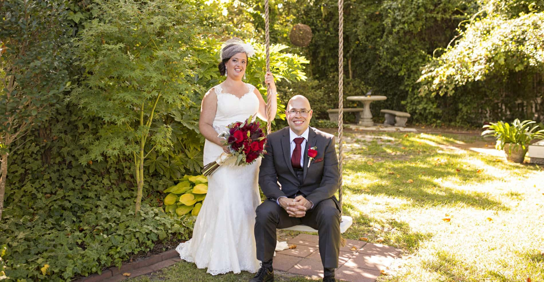 A groom sits on the treeswing with his beautiful bride standing beside him holding a lovely bouquet of red flowers