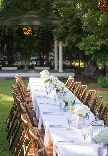 A long banquet table set out for an exterior wedding reception or banquet.