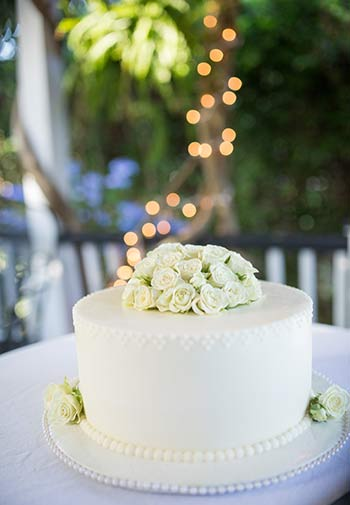 A beautifully simple single tier wedding cake with decorative flowers