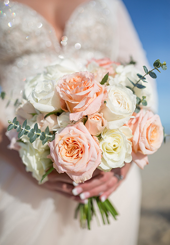 Peach and beige roses in a floral wedding bouquet.