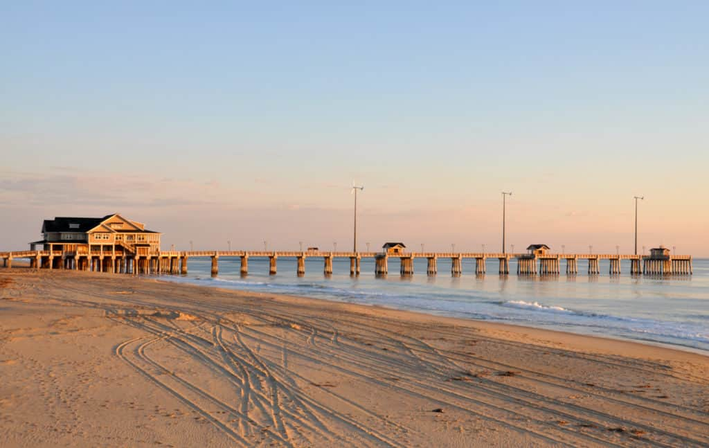 Beach view of pier in Nags Head North Carolina at sunset with blue yellow and pink skies