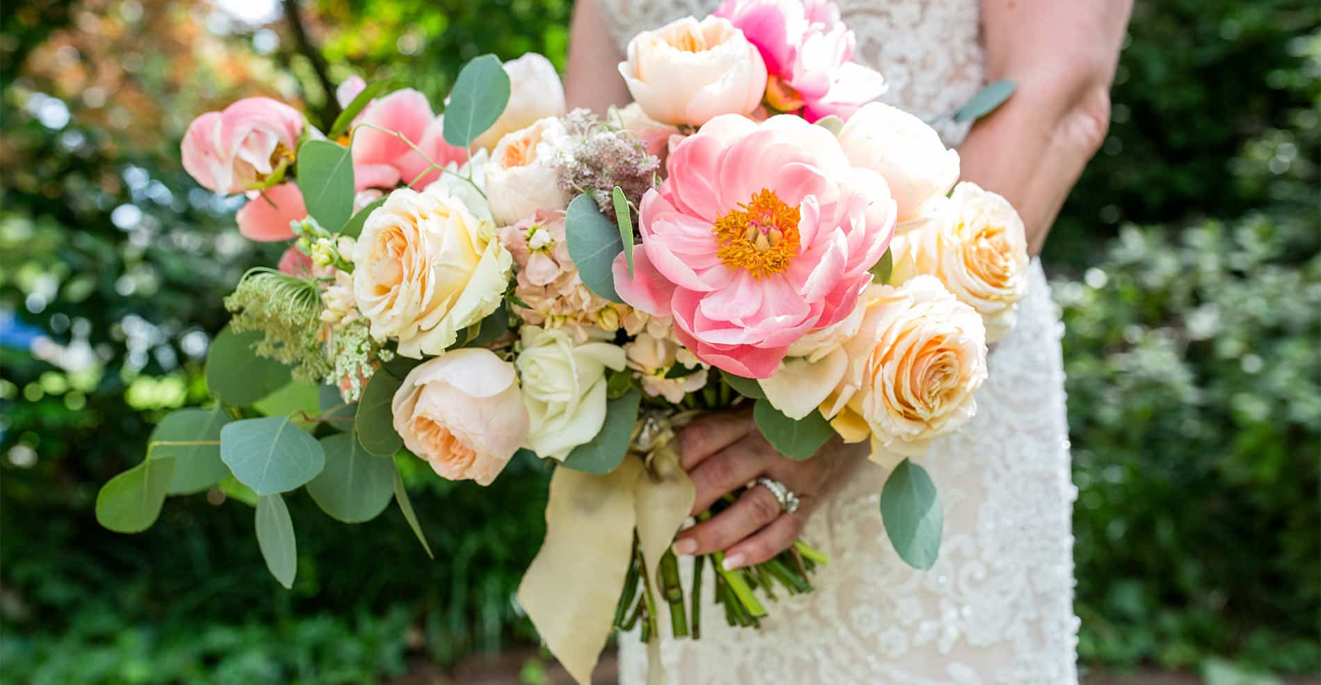 A pink wedding bouquet held by a bride, with flowers and pathway in background