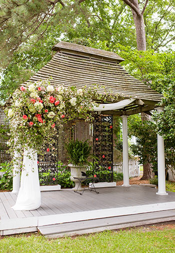 Gazebo with flowers draped decoratively down the pilars and back panal.