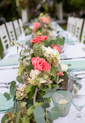 A banquet table with white chairs, set with placeholders and expansive floral center pieces line the length of the table.