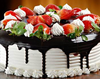 A delicious white cake with chocolate dripping down the sides and topped with red strawberries  and dollops of cream