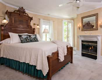 In a cream colored cozy room a Large white bed with green accents sits across from a cozy fireplace