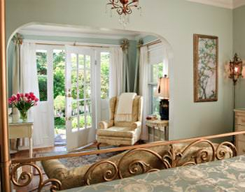 Beautiful and serene guest room with sage green walls, elegant bed, and bright sitting area overlooking natural green landcaping