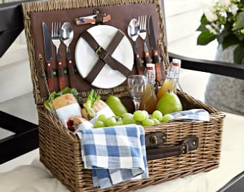 A brown wicker picnic basket sits open with sandwiches, green grapes and pears