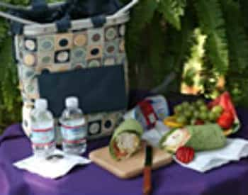 A blurry view of a picnic basket, two bottles of water and a green spinach wrap on a purple tablecloth