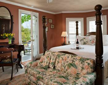 A view of a salmon colored room , a pink and green loveseat sets at the foot of the four-post bed