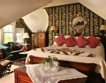 A cozy guestroom with floral wallpaper,has a white bed with red accents, a chest and small sitting area