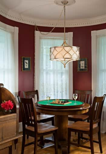 A small brown game table has a chess set ready to play in this burgundy room